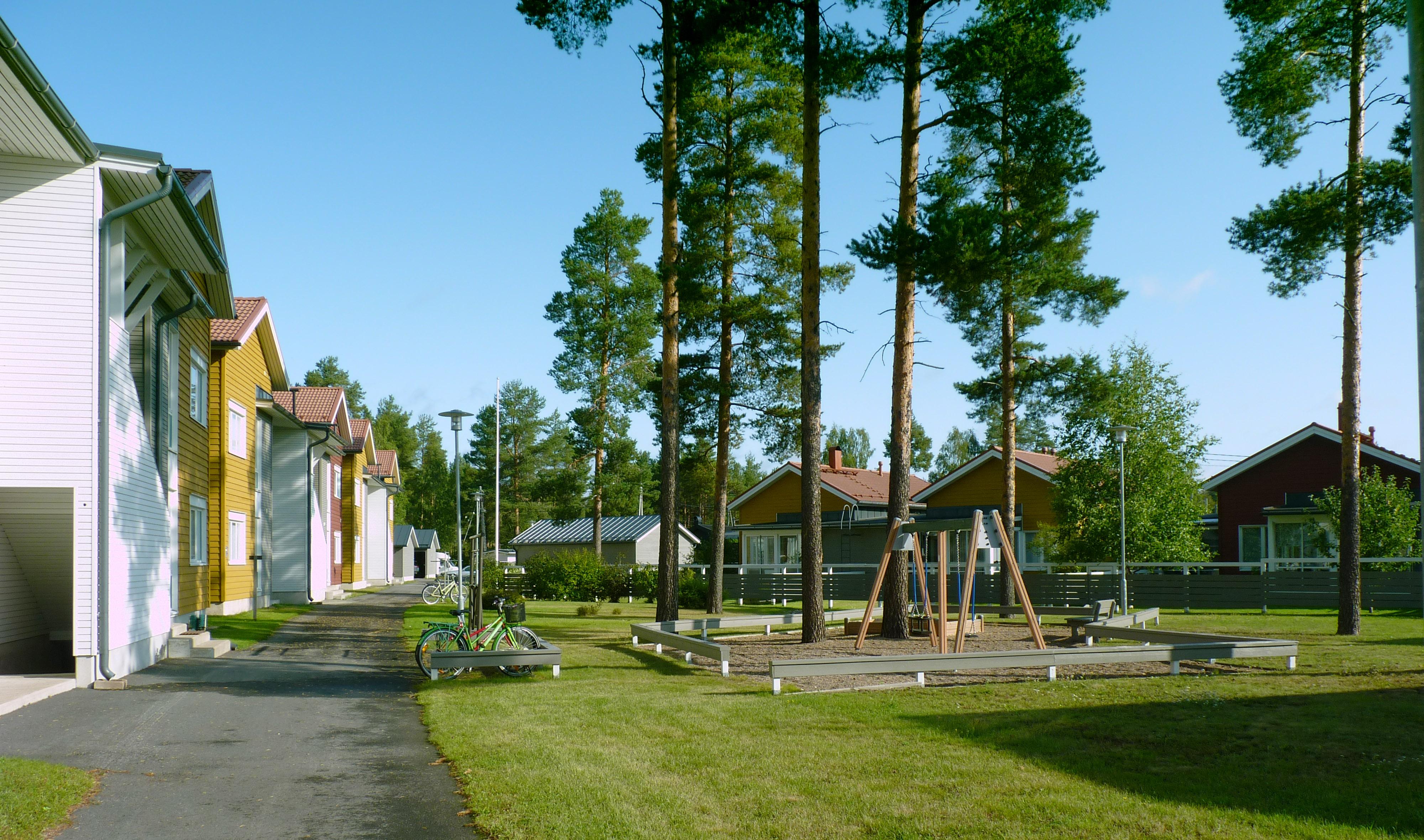 Kytkettyjen pientalojen rajaama piha, jossa on leikkipaikka, nurmea ja mäntyjä.