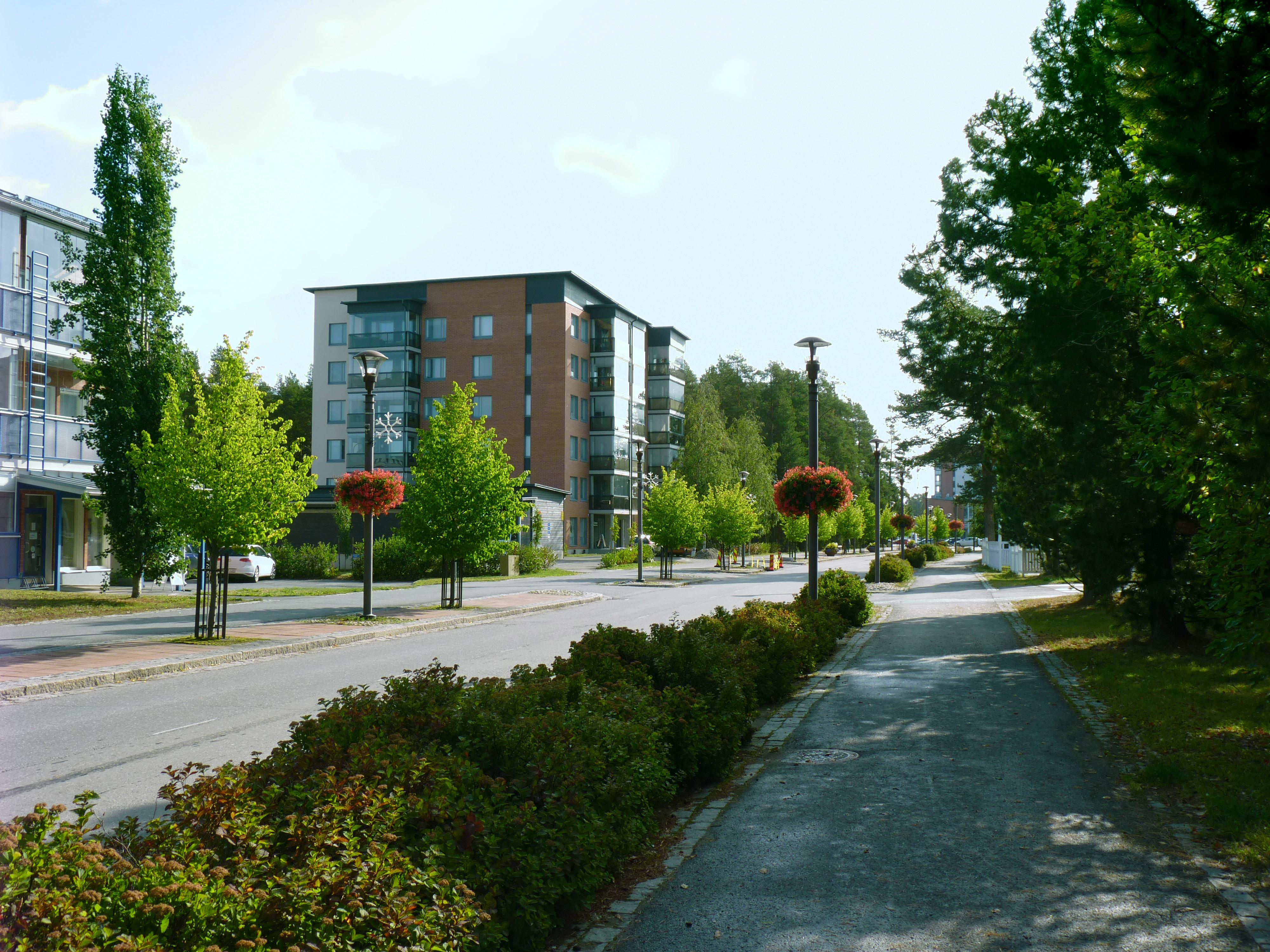 Kirkkotien näkymä. Vihreät istutukset ja katutilaa rajaavat kerrostalot.