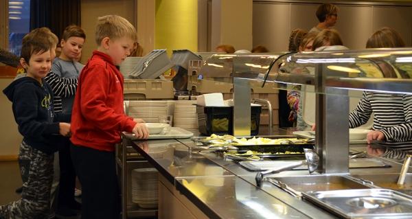 Kuvassa on ala-asteikäisiä poikia valitsemassa ruokaa ruokalan linjastolta.