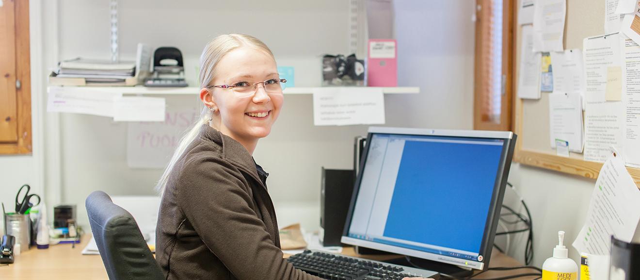Kunnan työntekijä istuu työpisteellään ja hymyilee kameralle.